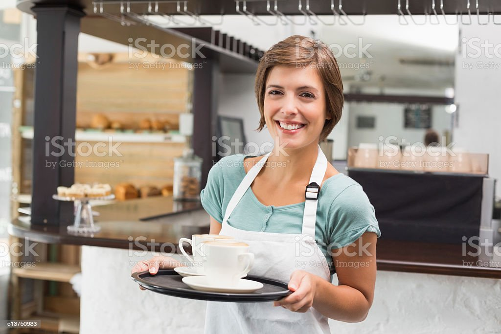 Waitress holding tray with cappuccinos stock photo