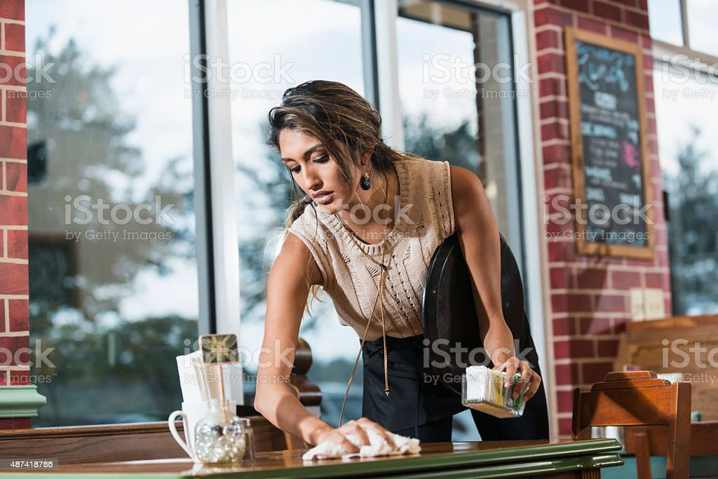 Waitress in a restaurant cleaning table with cloth stock photo