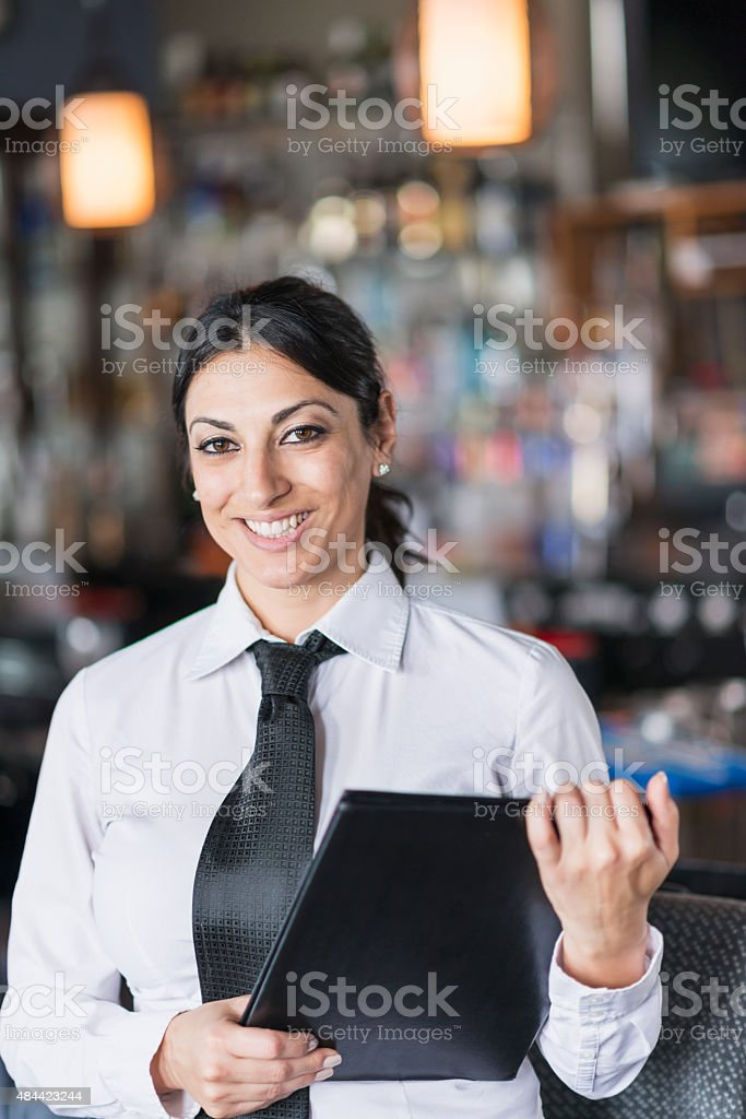 Waitress in a restaurant holding menu stock photo
