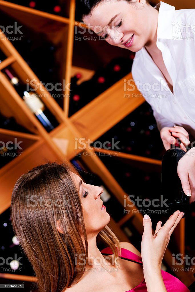 Waitress in restaurant offering red wine royalty-free stock photo