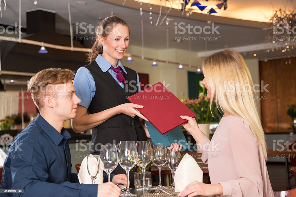 Waitress in restaurant presenting the menu to two guests stock photo