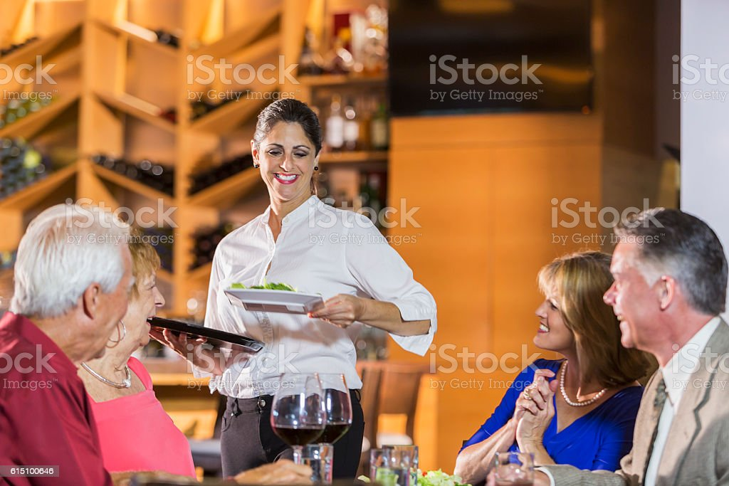 Waitress in restaurant serving food to customers stock photo