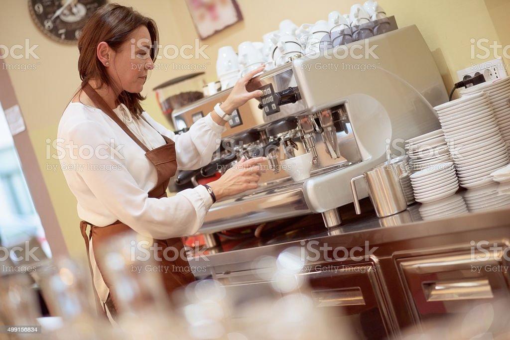 Waitress making coffee using a coffee maker stock photo