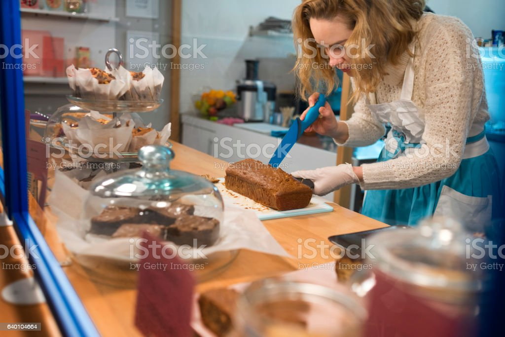 waitress measuring where to cut exactly the cake stock photo