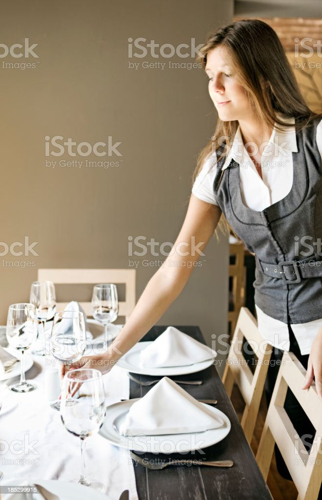 Waitress placing glasses on table in restaurant stock photo