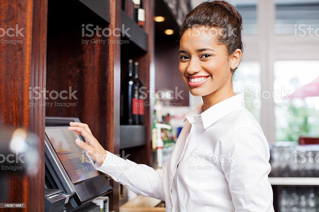 Waitress Preparing Bill At Cash Register In Restaurant stock photo