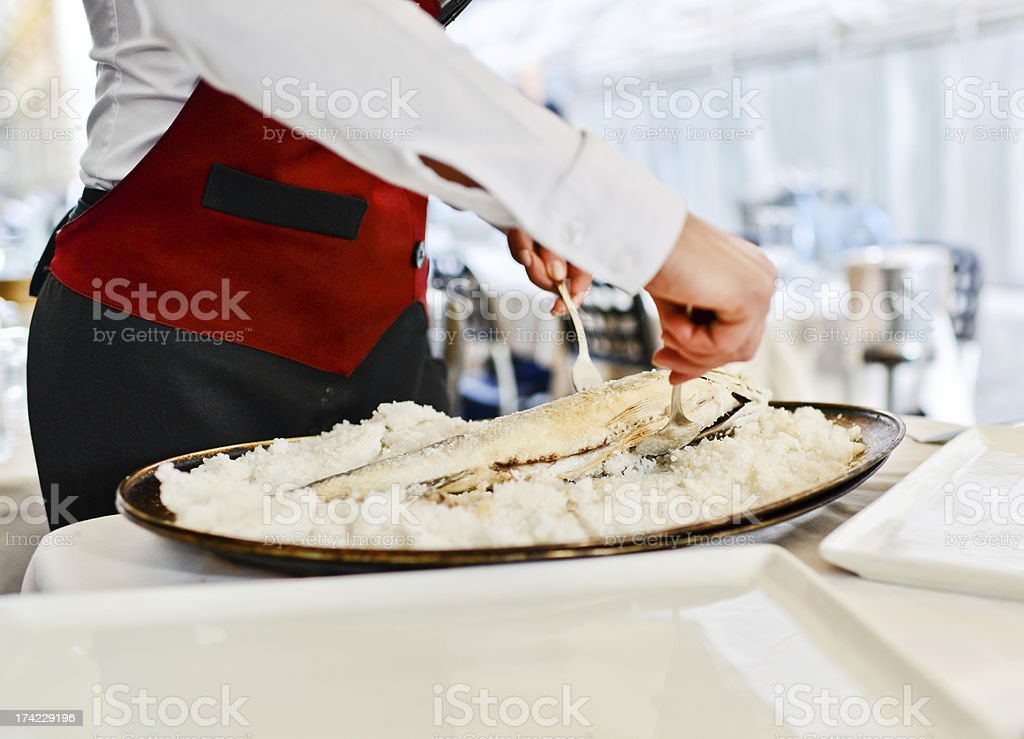 Waitress Preparing Seabass baked in a salt crust royalty-free stock photo