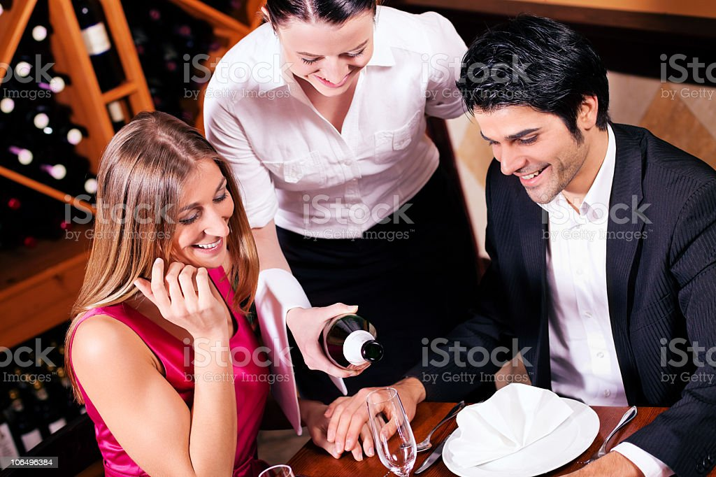 Waitress refilling a couples glasses of champagne royalty-free stock photo