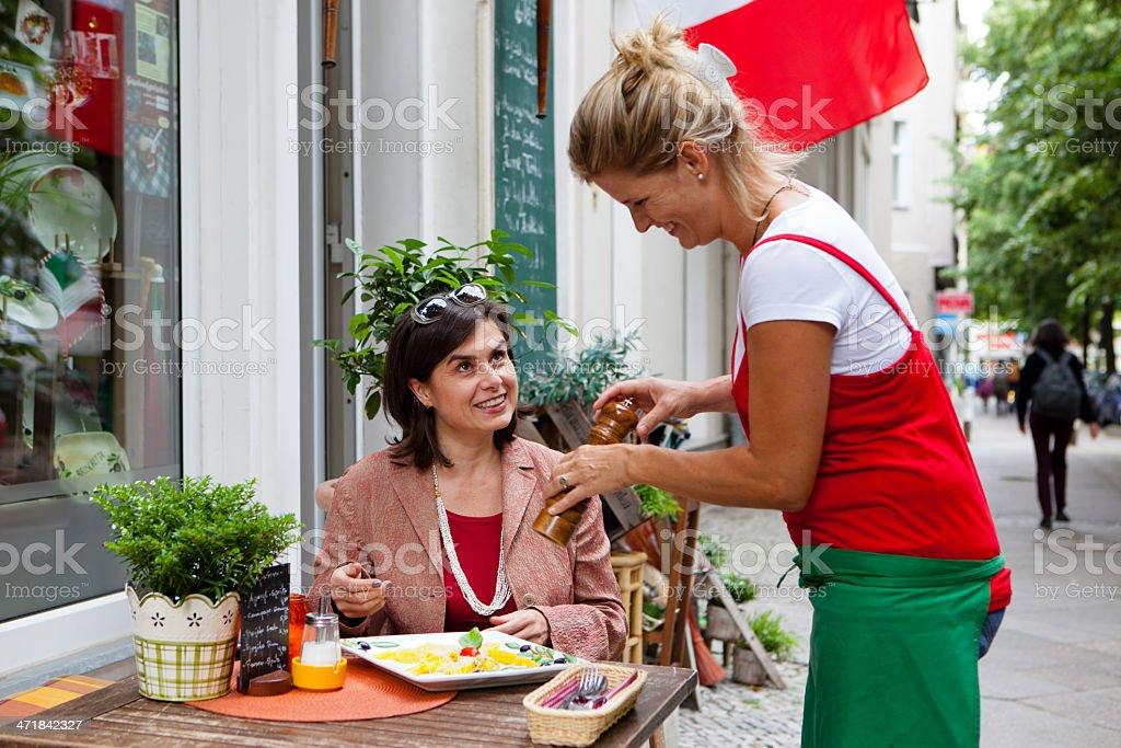 waitress serves the dish in a small italian restaurant royalty-free stock photo