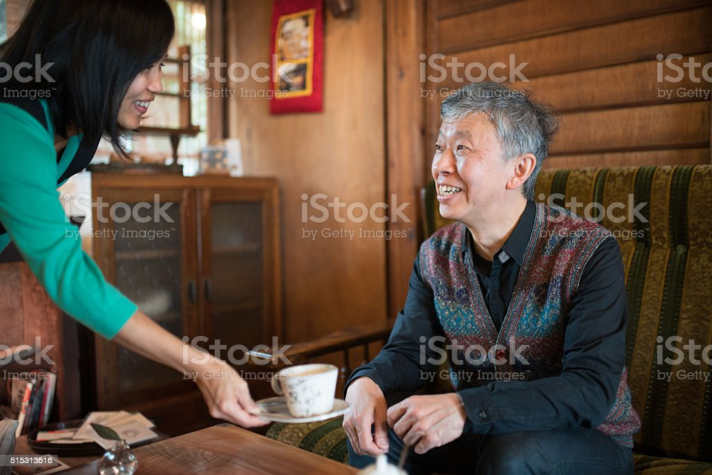 Waitress serving a cup of coffee to a senior customer stock photo