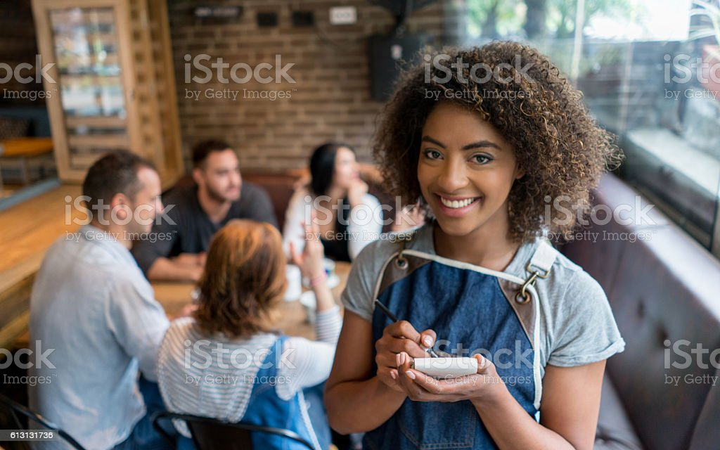 Waitress serving a group of friends at a restaurant stock photo