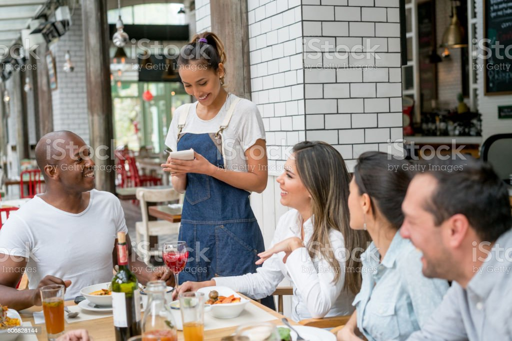 Waitress serving a group of people at a restaurant stock photo