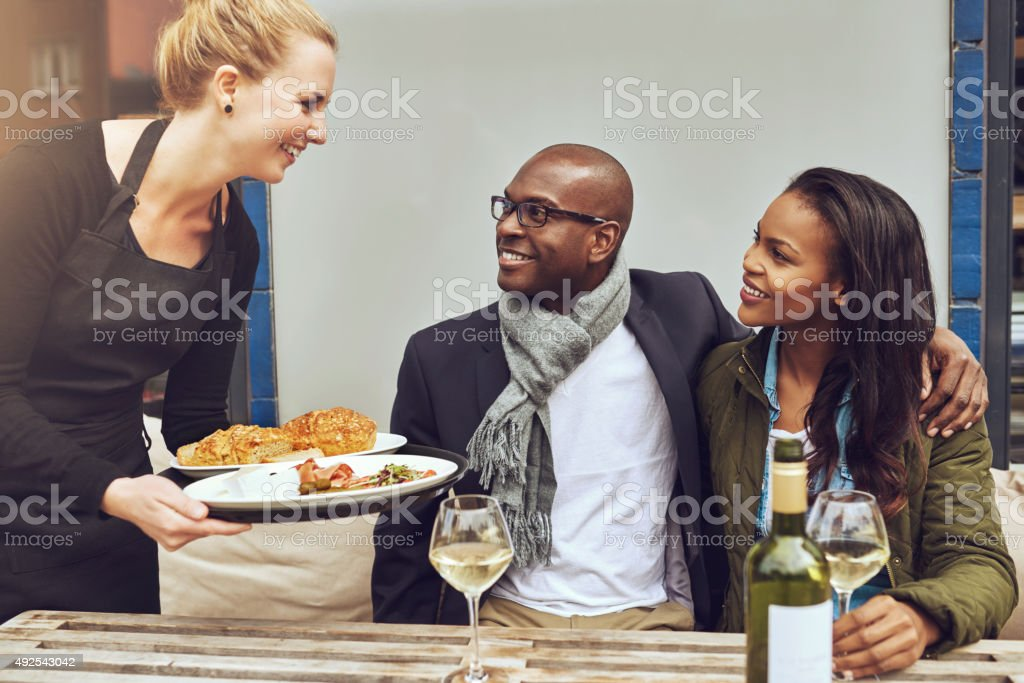 Waitress serving an African American couple dinner stock photo