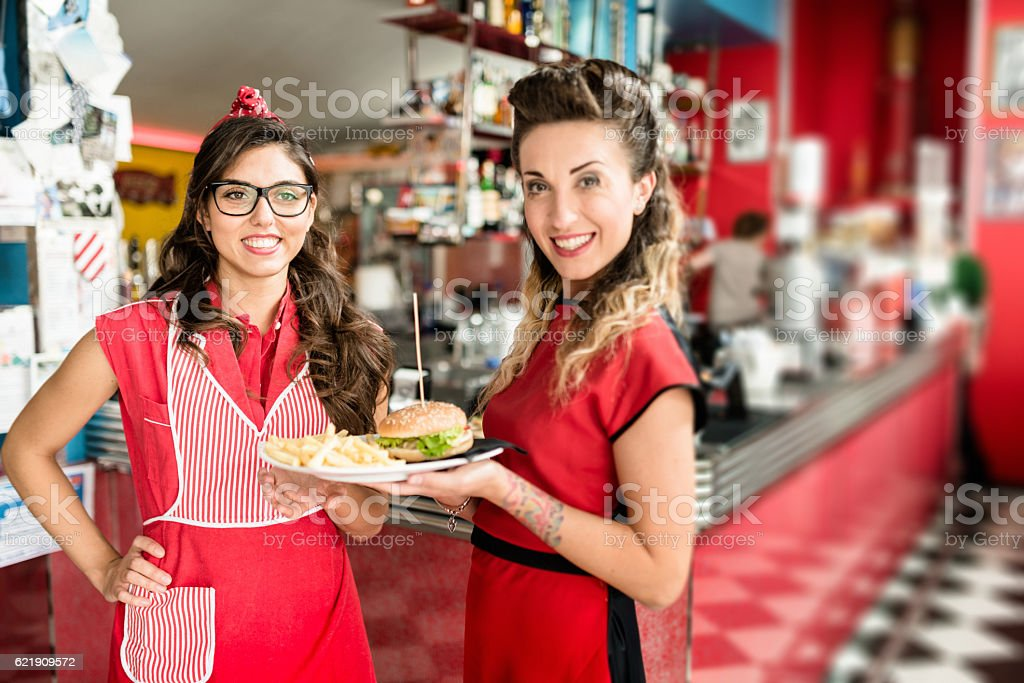 waitress serving an hamburger with french fries in a cafe stock photo