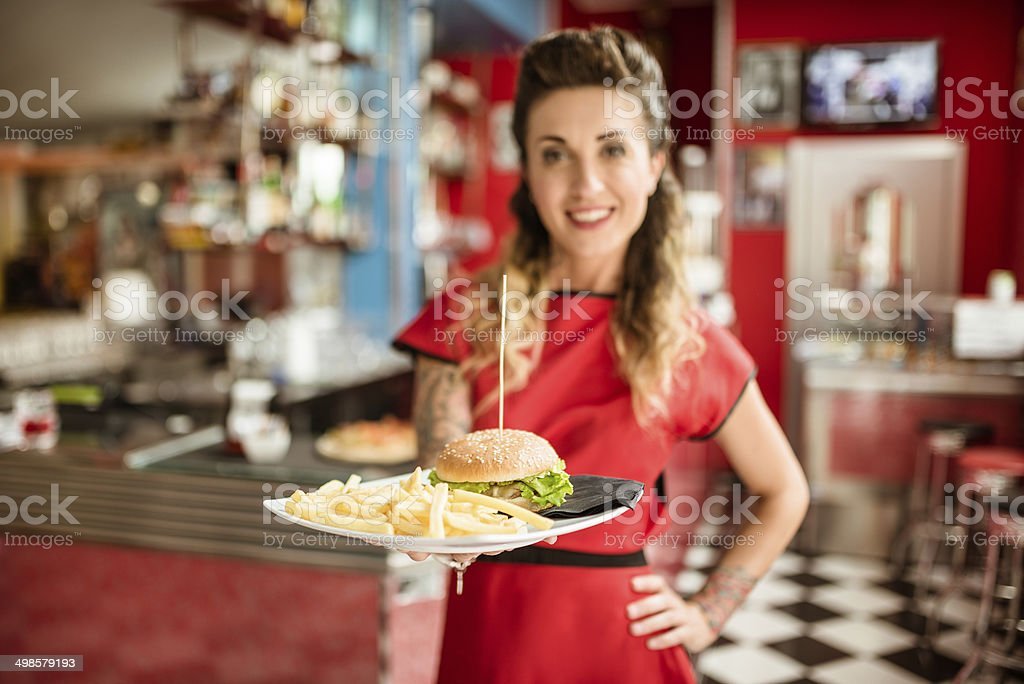 waitress serving an hamburger with french fries stock photo