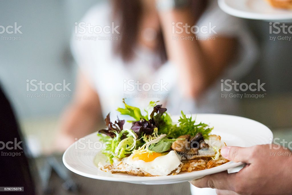 Waitress serving breakfast meal stock photo