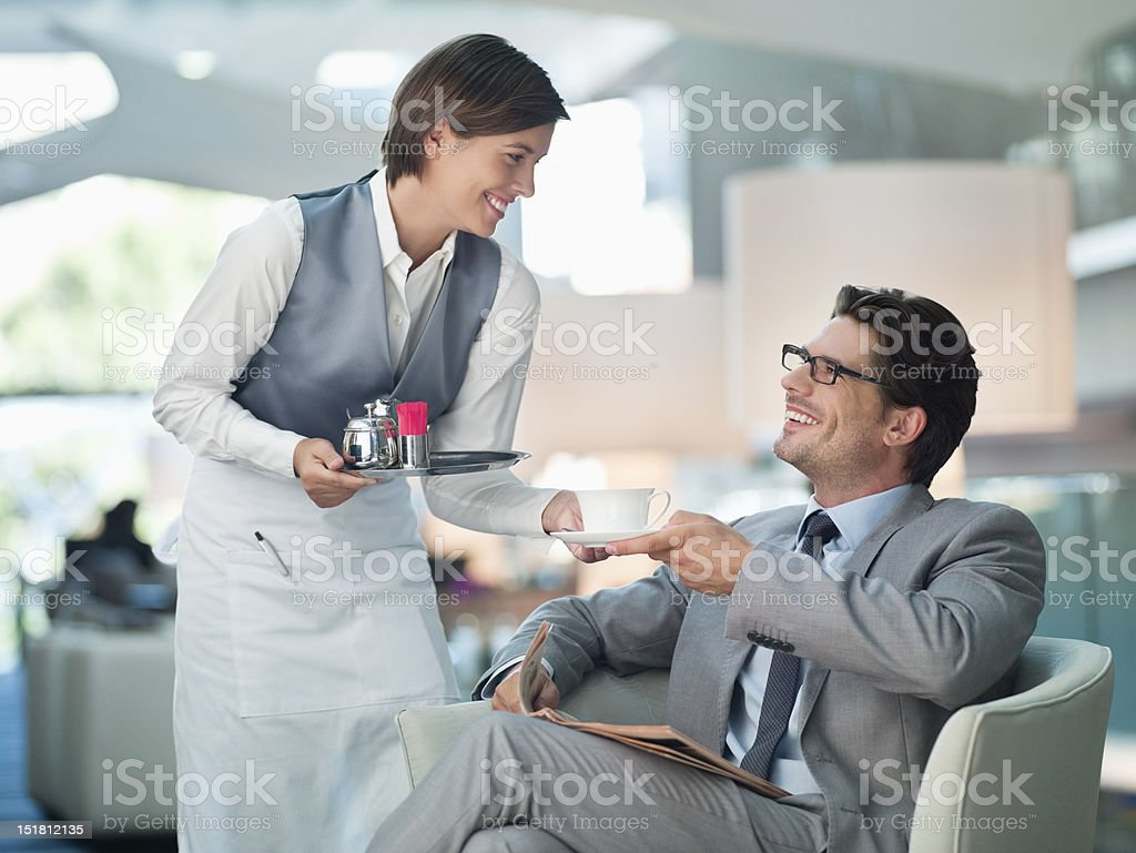 Waitress serving businessman cup of coffee in hotel lounge stock photo