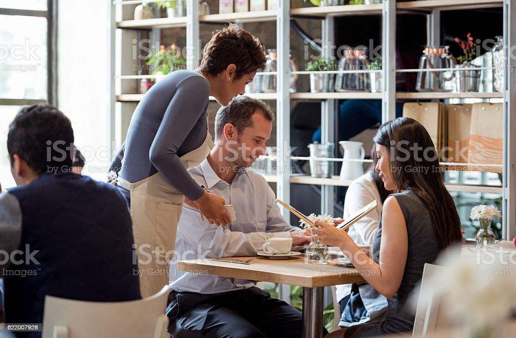 Waitress serving couple at a restaurant stock photo