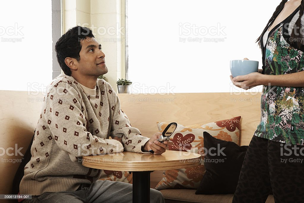 Waitress serving cup of coffee to young man in cafe, side view stock photo