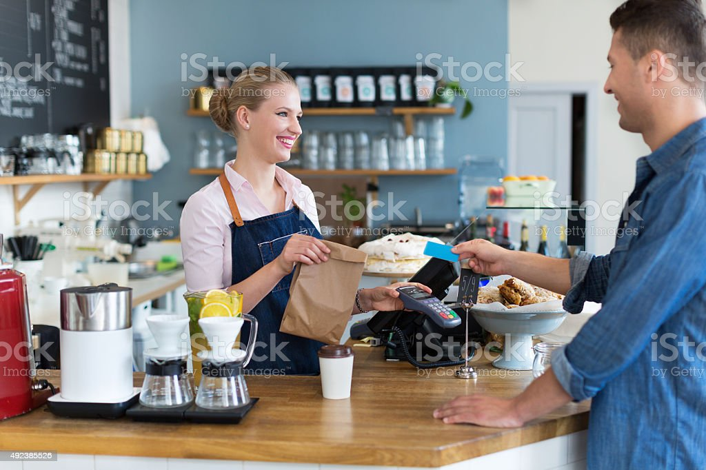 Waitress serving customer at the coffee shop stock photo