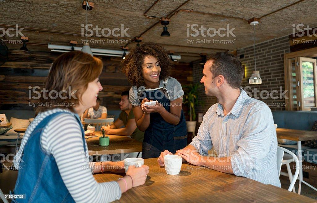 Waitress serving customers at a restaurant stock photo