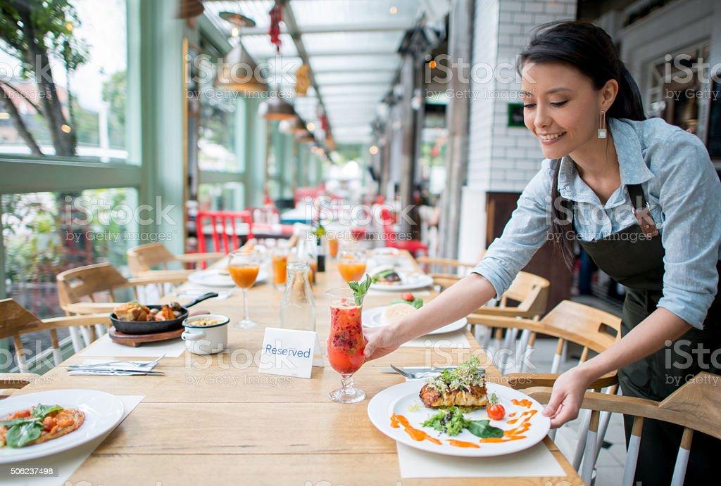 Waitress serving dinner at a restaurant stock photo