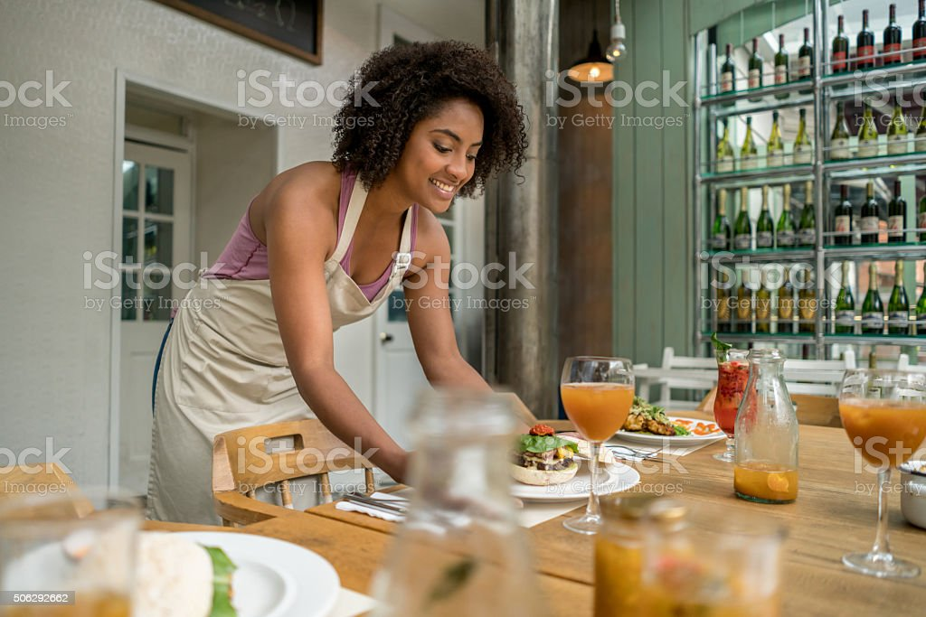 Waitress serving dinner at a restaurant stock photo
