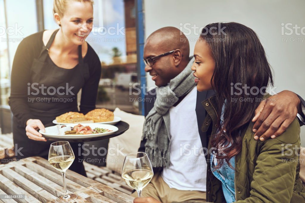 Waitress serving food to an African couple stock photo