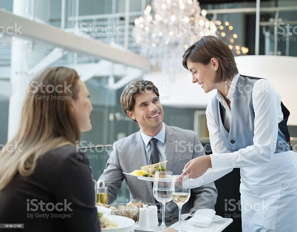 Waitress serving food to couple in restaurant stock photo