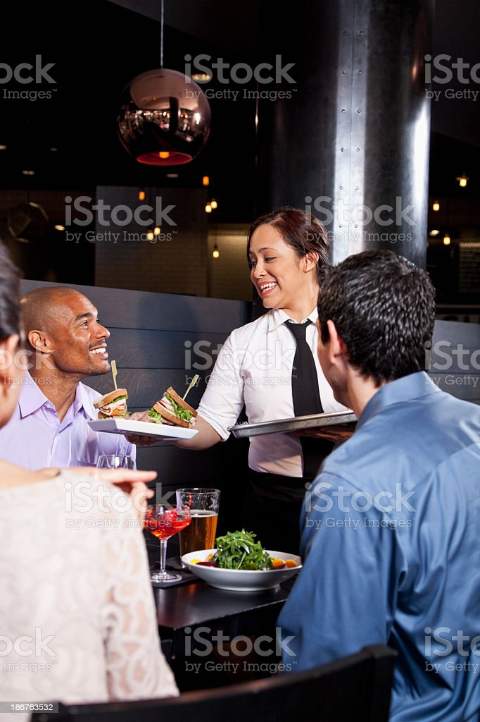 Waitress serving food to diners royalty-free stock photo