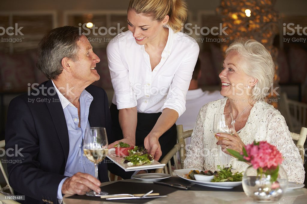Waitress Serving Food To Senior Couple In Restaurant stock photo