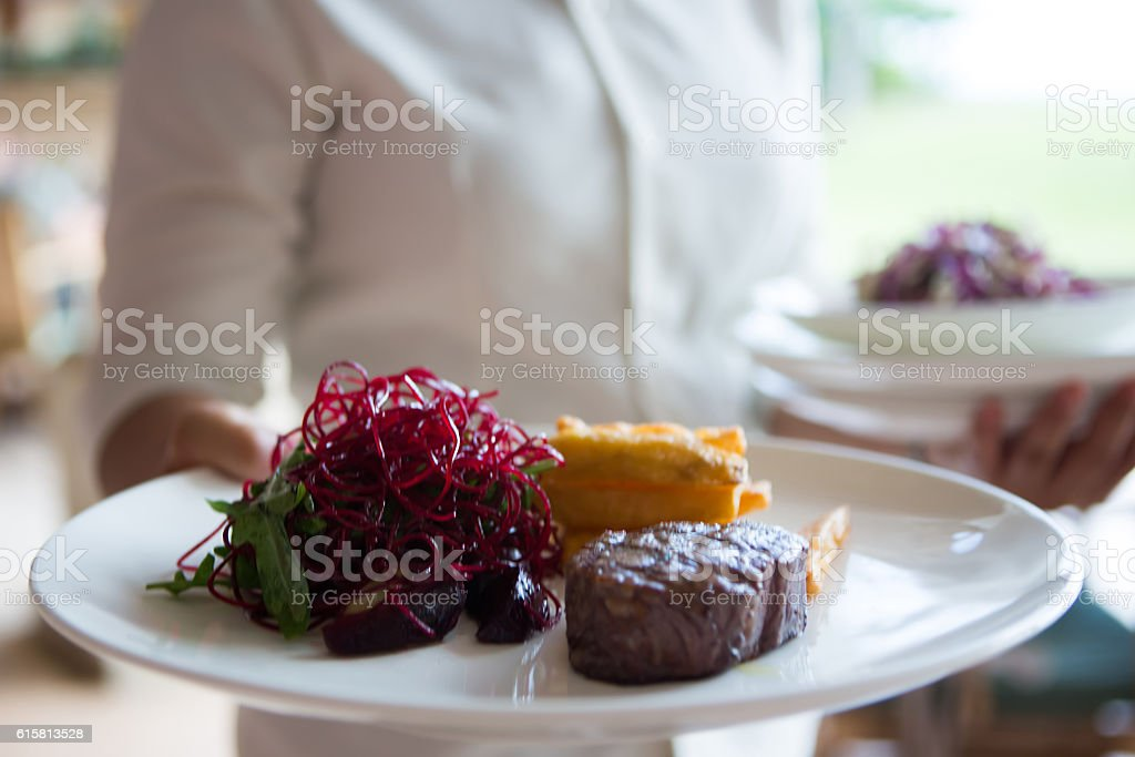 Waitress serving gourmet food stock photo