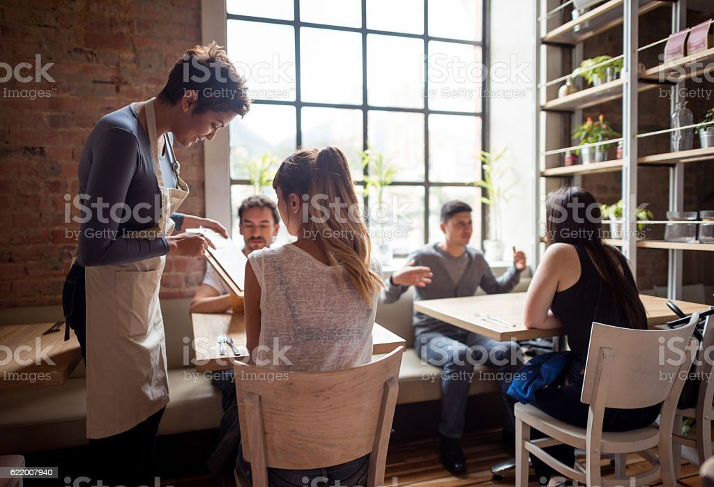 Waitress serving people at a restaurant stock photo