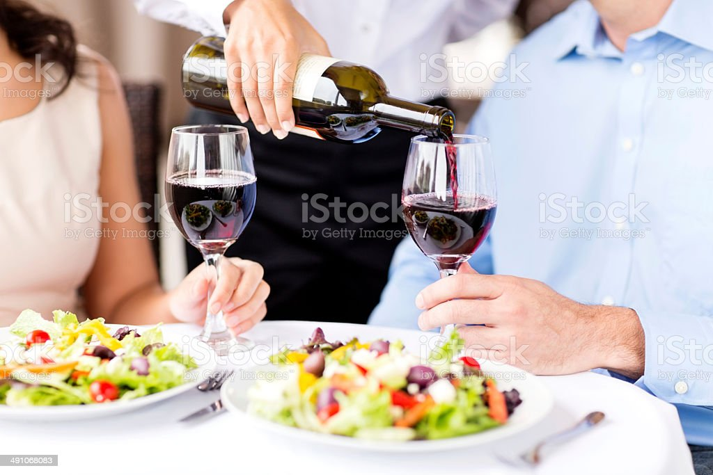 Waitress Serving Red Wine To Couple At Restaurant stock photo