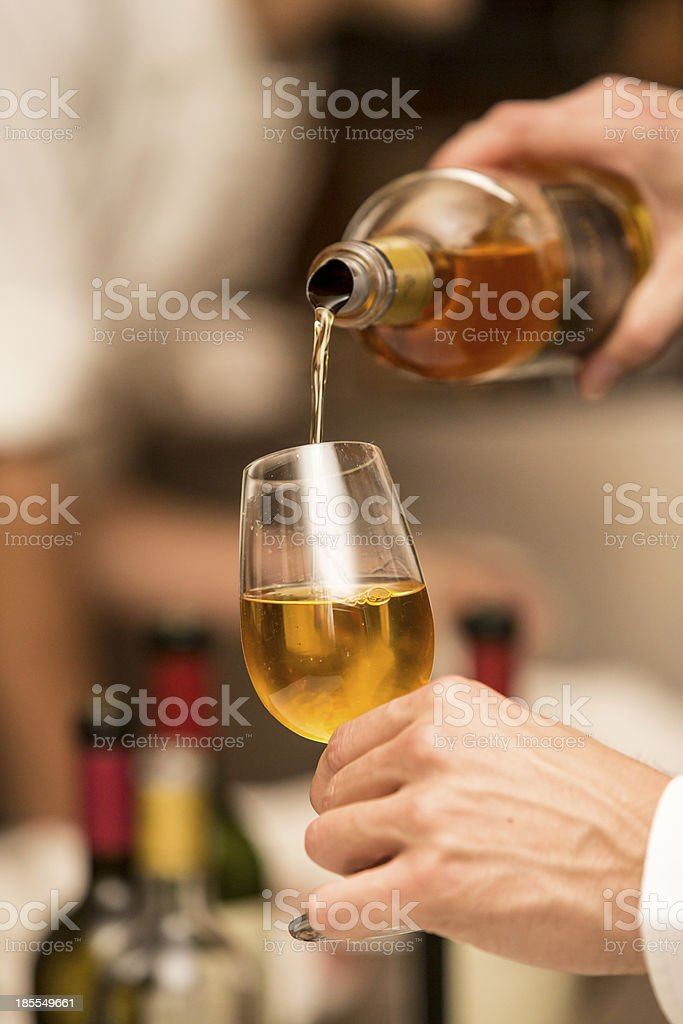 Waitress serving sweet golden wine on a cup, glass. stock photo