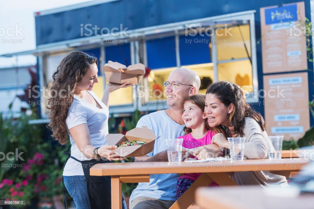 Waitress serving to customers outside food truck stock photo