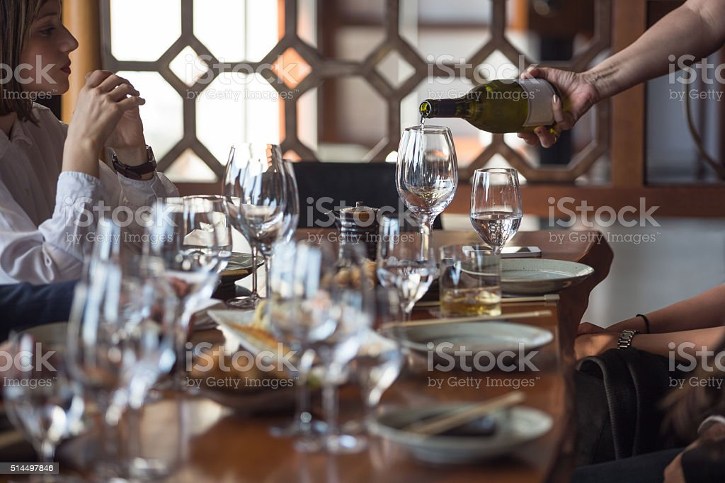 Waitress serving white wine to a group of friends in restaurant