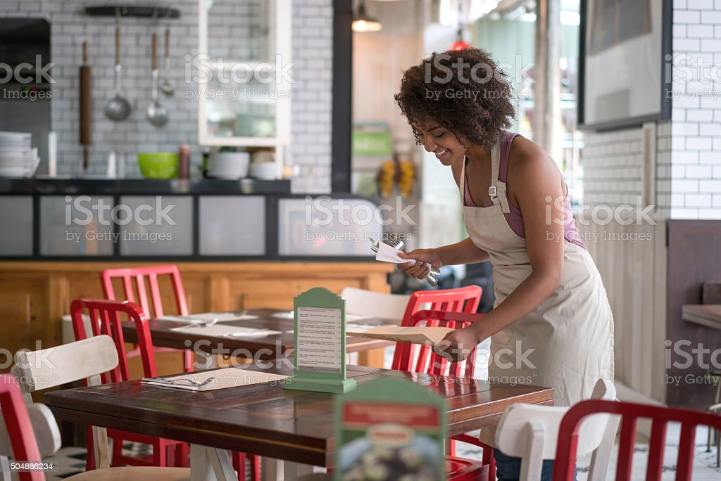 Waitress setting a table at a restaurant stock photo