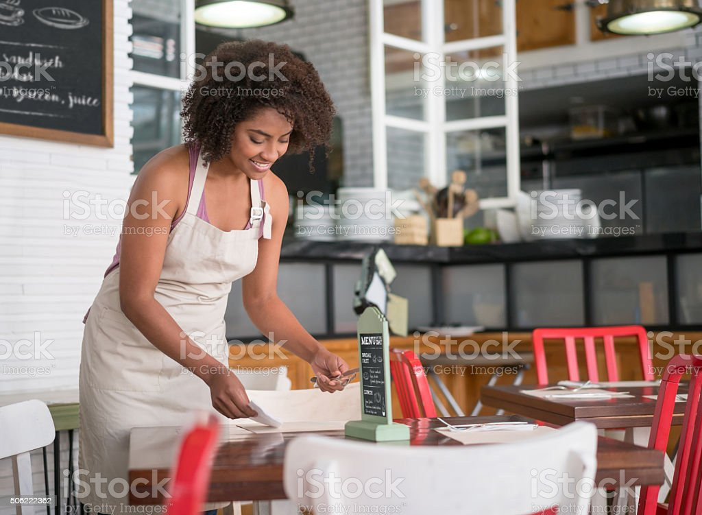 Waitress setting the table at a restaurant stock photo