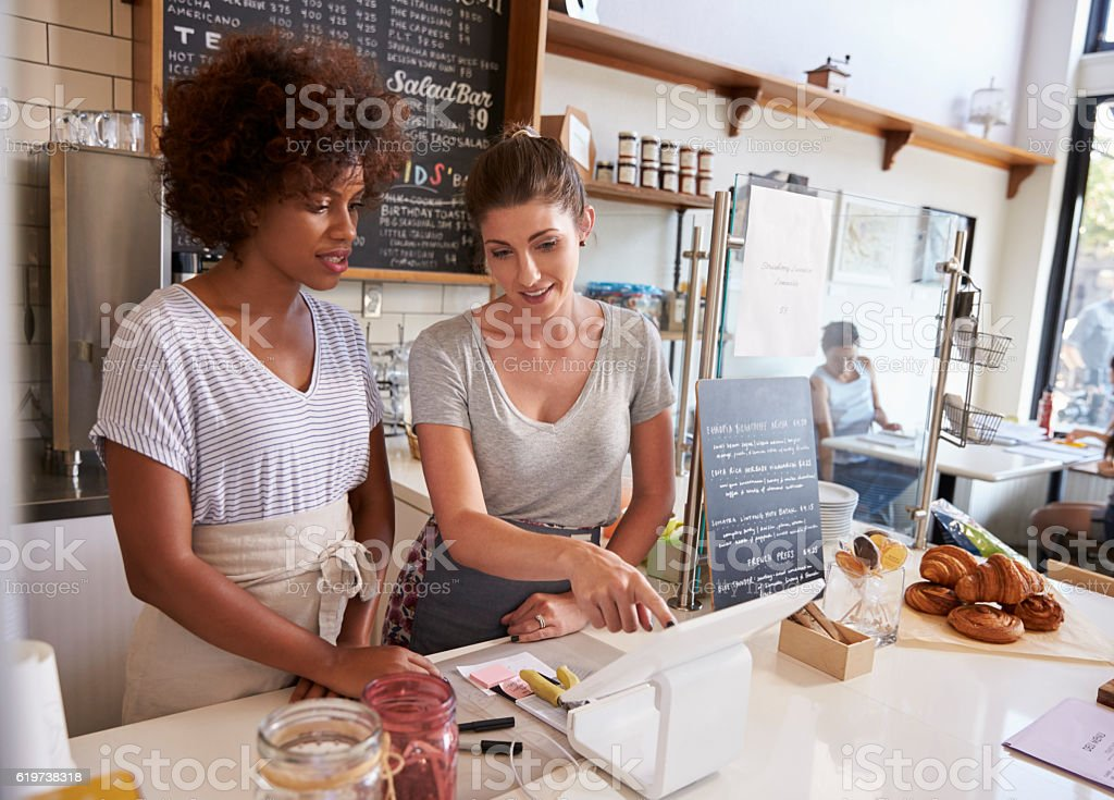 Waitress showing new employee the till at a coffee shop stock photo