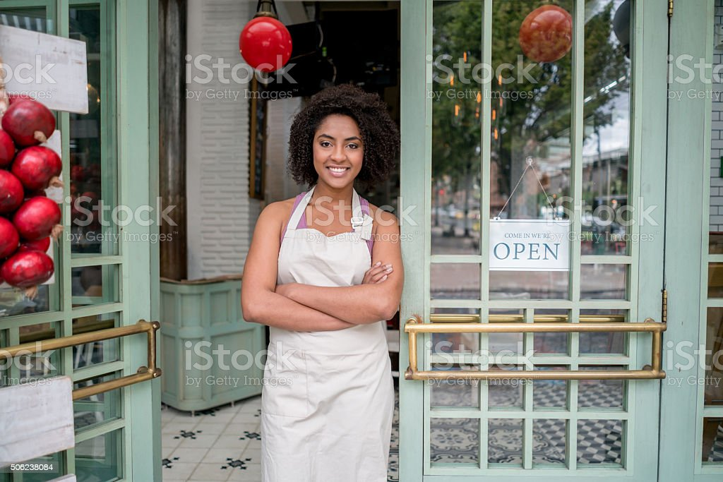 Waitress standing at the door of a restaurant stock photo