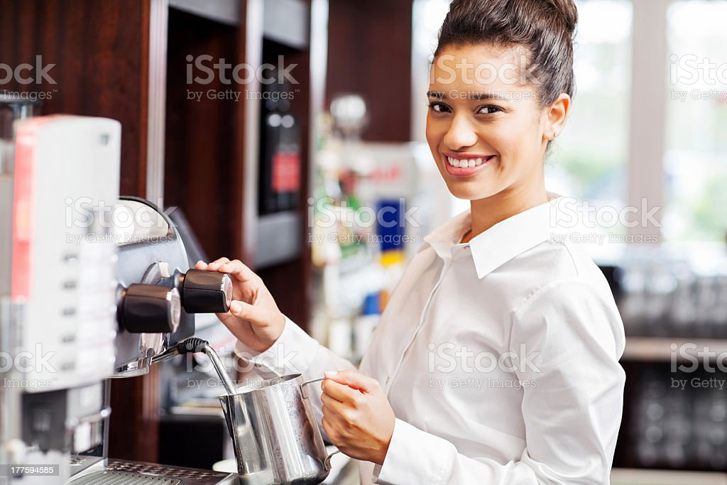 Waitress Steaming Milk From Coffee Maker In Restaurant royalty-free stock photo