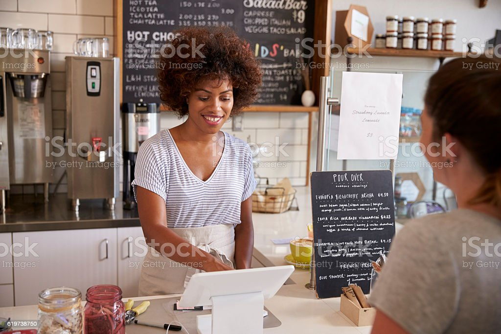 Waitress taking a customer's order at till in a coffee shop stock photo