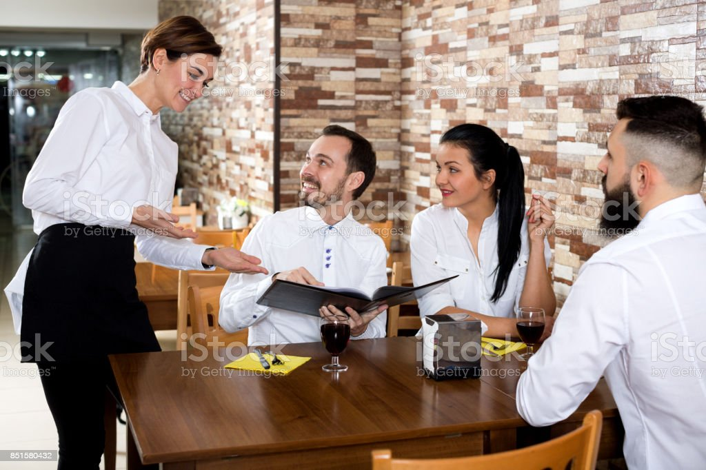 Waitress taking order at table of people stock photo