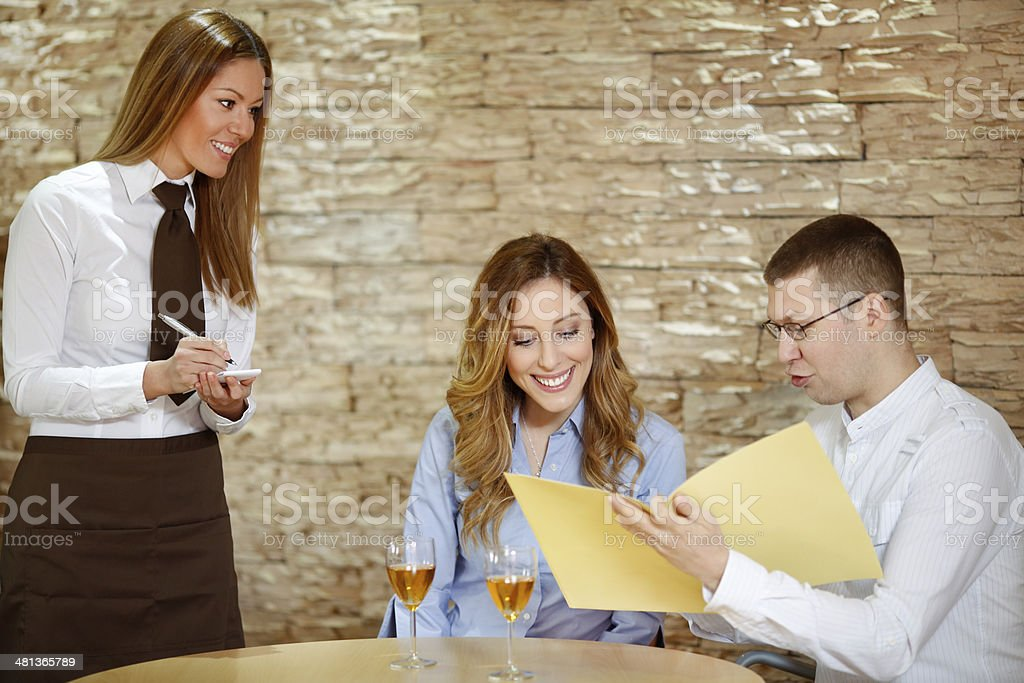 Waitress taking order from young couple. stock photo