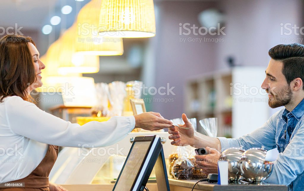 Waitress taking payment from customer in a cafe stock photo