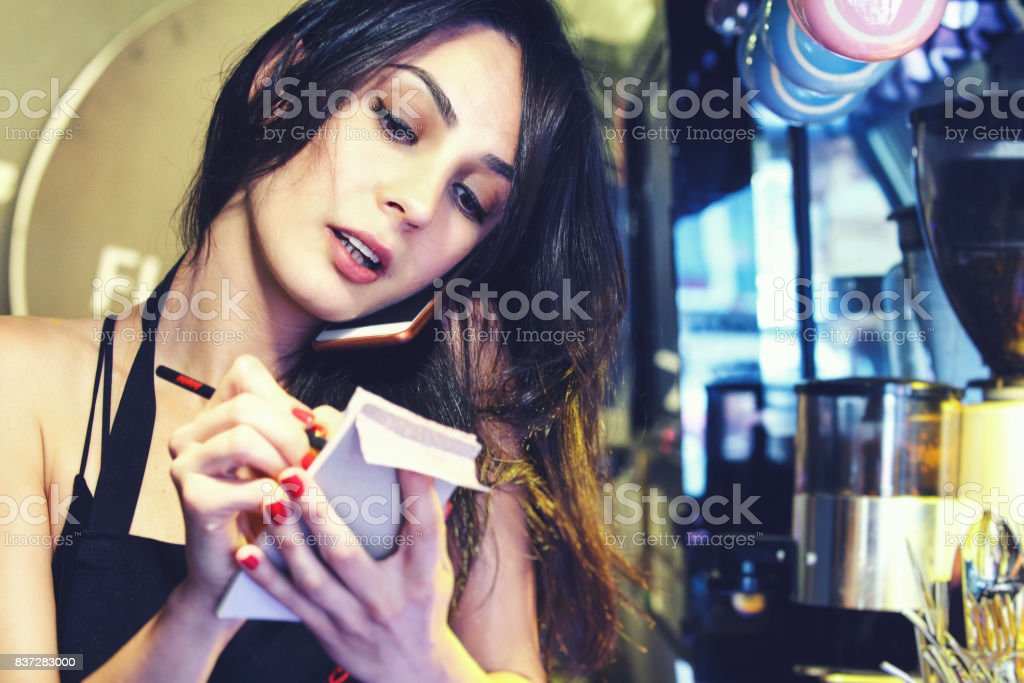 Waitress talking on the phone at a restaurant stock photo