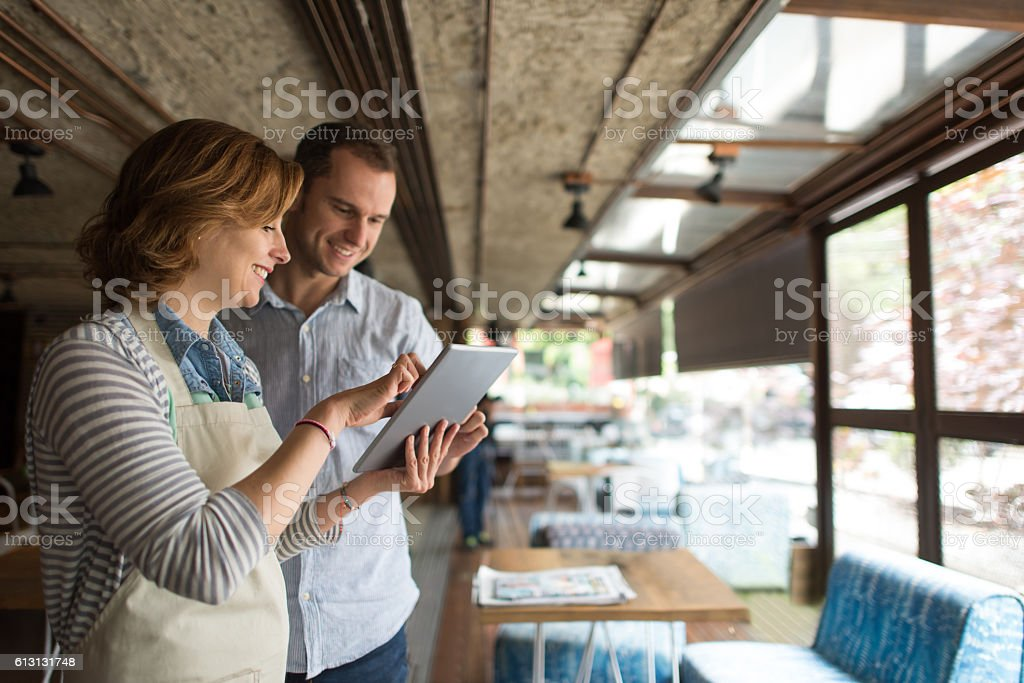 Waitress talking to business owner at a restaurant stock photo