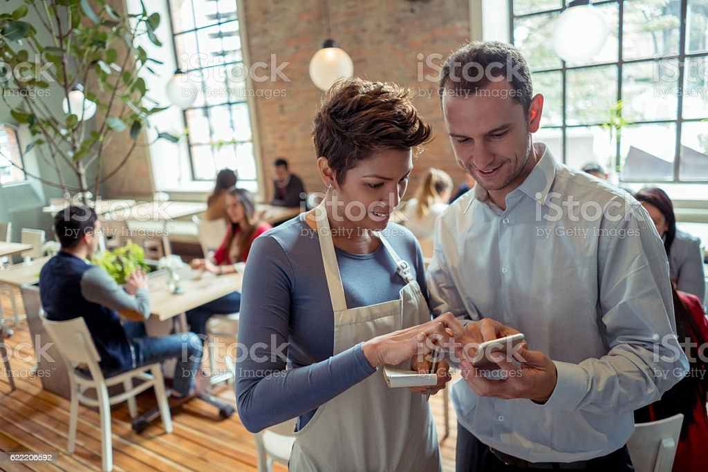 Waitress talking to manager at a restaurant stock photo