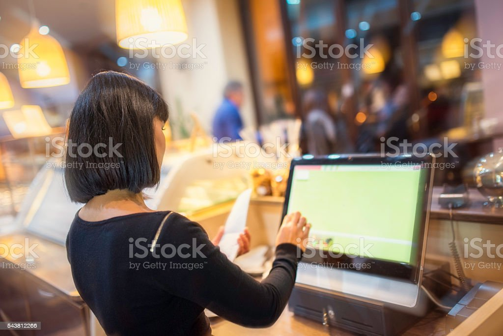 Waitress using touchscreen computer at the bar counter stock photo